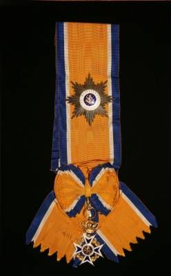 Star and riband of a Knight Grand Cross of the Order of Orange-Nassau. The badge of the Order is a blue-enamelled, white enamel-bordered Maltese Cross, in gilt for the officers and above, in silver for knights and members. The obverse central disc has the lion from the Dutch coat-of-arms of the Netherlands in gold and blue enamel, surrounded by a white enamel ring bearing the Dutch national motto Je Maintiendrai (I shall maintain). The badge hangs from a royal crown.
