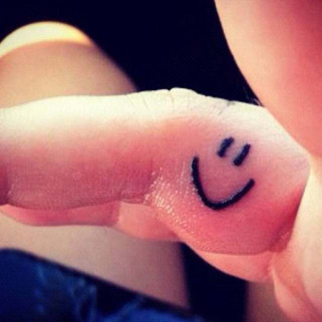 smiley face tattoo on the inside of my right ring finger! :)