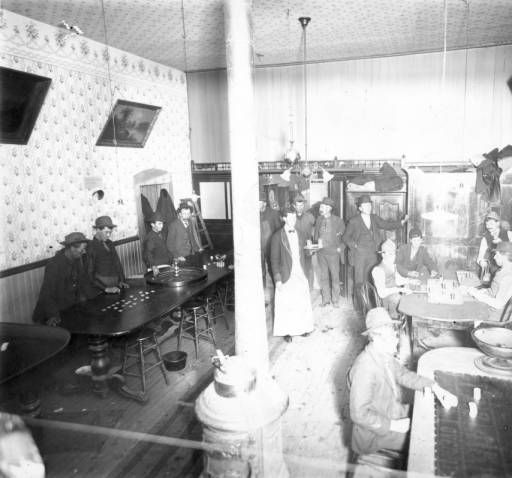Interior view of a saloon in Leadville (Lake County), Colorado; shows men gambling with poker chips, a roulette wheel, and slot machines. A man in an apron carries a tray of beer glasses; decor includes spittoons, framed art, and a stove.  Date [between 1880 and 1910]