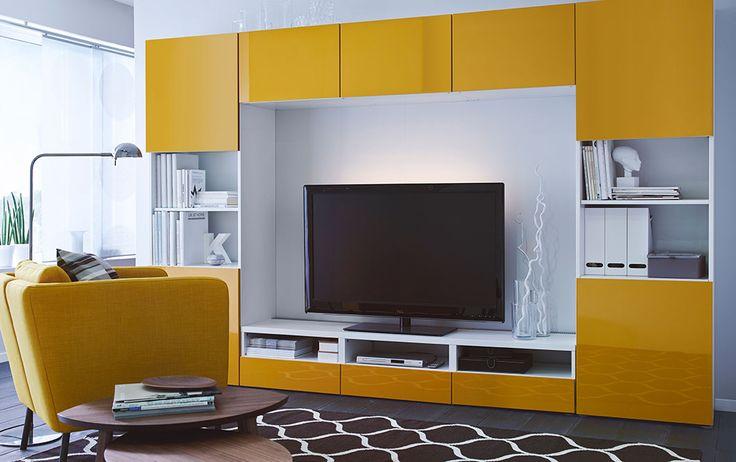 Séjour avec une grande combinaison média et divertissement, composée d'un banc TV blanc et d'étagères combinées à des portes en verre transparent et des portes et faces de tiroirs en jaune brillant