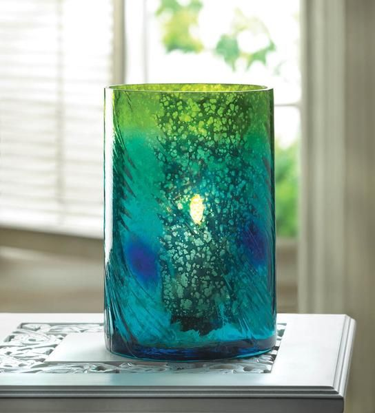 "Vases and Accents Home Locomotion The colors of the swirling Mediterranean tide are captured in this vases entrancing details. The subtle texture of a swift current and bubbling mixture of greens, blues and golds make this a standout centerpiece. Use this gorgeous vase as a candleholder, fill it with glass stones, or place on your dining table for a simply dramatic centerpiece. Candle not included. Item weight: 1.80lbsItem dimensions: 4.63"" W x 7.13"" H x 4.63"" LMaterials: Glass..."