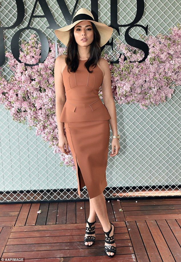 Racing ready: Jessica Gomes certianly stood out at the BMW Caulfield Cup in Melbourne on Saturday in a striking hat and terracotta coloured dress