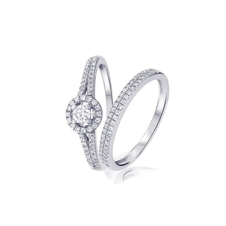 Zelda   est une bague de fiançailles est en or blanc 18 carats. D'un poids de 2.2 grammes, ce solitaire est serti d'un diamant rond de 0,10 carat et de 0.19 carat de diamants d'acccompagnement, de couleur H et de pureté SI.       Nanou  est une alliance en or blanc est sertie de 0.15 carat de diamants ronds de couleur G et de pureté VS pour un éclat somptueux symbolisant une vie à deux.