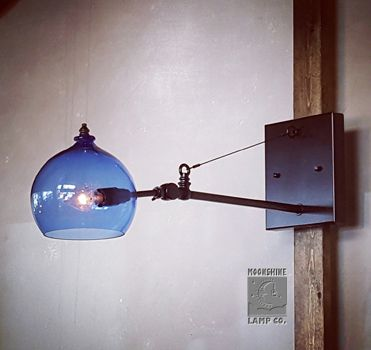 The Clovis, is our newest industrial style wall sconce.  This would look good in your modern dwell home or your old time saloon style restaurant or bar.  That blown glass orb comes in a variety of colors.