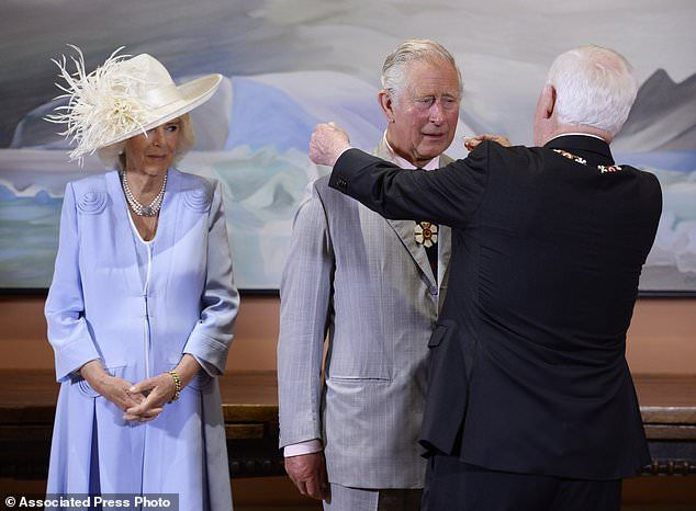 Prince Charles, center, receives the Extraordinary Companion to the Order of Canada medal from Governor General David Johnston as Camilla Duchess of Cornwall looks on at Rideau Hall in Ottawa on Saturday, July 1, 2017. (Adrian Wyld/The Canadian Press via AP)