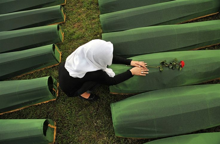 A Bosnian Muslim woman mourns over the casket of a relative, one of 409 newly-identified victms of the 1995 Srebrenica massacre, at the Potocari Memorial Center in Srebrenica, Bosnia, on July 10, the day before Thursday's burial ceremony.