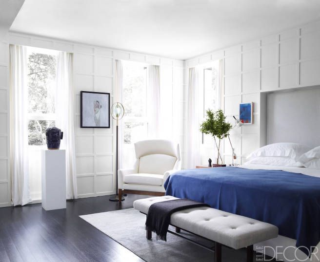 Nice paneling. A striking pallet of black, white and royal blue sets a fresh tone in this airy Manhattan bedroom. The bench is 1960s Harvey Probber, the armchair by Jens Risom and the floor lamp by Max Ingrand. Photo by Simon Upton via Elle Decor.