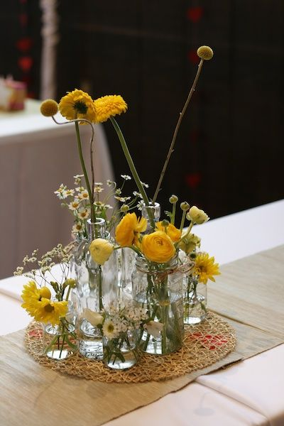 Three-level centerpiece in bourbon jars, mason jars, and baby food jars. Flowers include craspedia, gerberas, ranunculus, feverfew, statice, daisy mums.