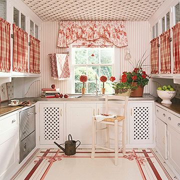 Wallpaper Adds Style -  Wallpaper reminiscent of fabric covers the walls of this kitchen, emphasizing its country style. The simple pattern coordinates with the plaid and floral fabrics at the window and the cabinets and repeats the stripes found in the rug. The linear element also balances the lattice used on the ceiling.
