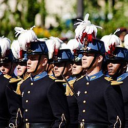 """The École Spéciale Militaire de Saint-Cyr (ESM, literally the """"Special Military School of Saint-Cyr"""") is the foremost French military academy. It is often referred to as Saint-Cyr (French pronunciation: [sɛ̃ siʁ]). Its motto is """"Ils s'instruisent pour vaincre"""": literally """"They study to vanquish"""" or """"Training for victory"""". French cadet officers are called """"saint-cyriens"""", or """"cyrards"""". The École Spéciale Militaire de Saint-Cyr is located in Coëtquidan in Guer, Morbihan department, Brittany,"""