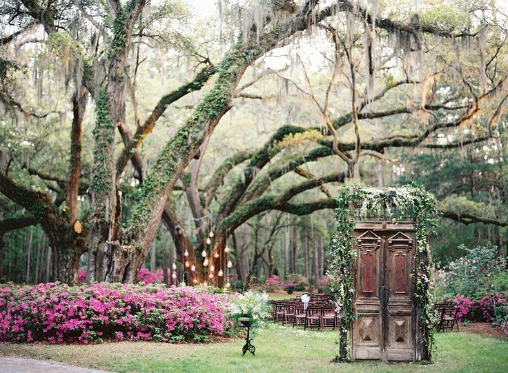 rustic doors at ceremony entrance, hanging lights at the alter in front of an old oak tree http://itgirlweddings.com/cameran-eubanks-southern-wedding/