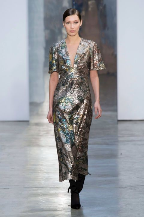 Herrera did not hold back on the extra details — the sequins, frills, ribbons, bows — that define feminine glamour, but she and her team use a restrained hand. So the all-over shiny dress on Bella Hadid came out in a spare v-neck silhouette with near t-shirt sleeves. Zero jewelry and opaque black tights and wrap-up heels.