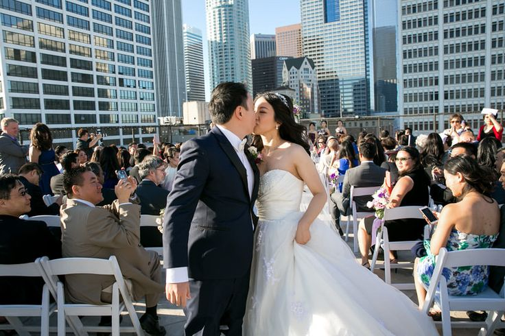 Newly wed kissing at the rooftop