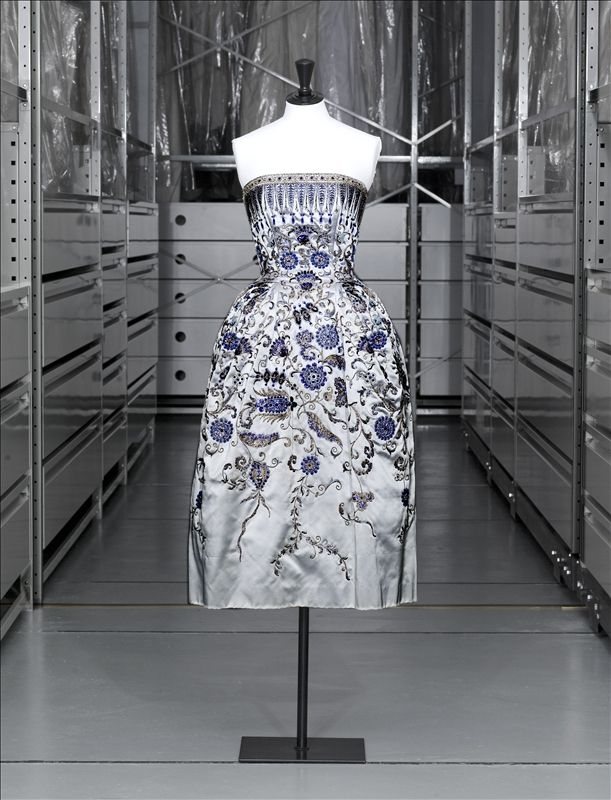 'PALMYRE' evening dress, Christian Dior. Various apt shades of blue – 'cerulean', 'smoke' and 'ice' – were used for the stylised floral and other motifs embroidered with pearls, paillettes and crystal. The dress's bustier is accentuated by serried ranks of palmettos. Autumn-Winter 1952–1953