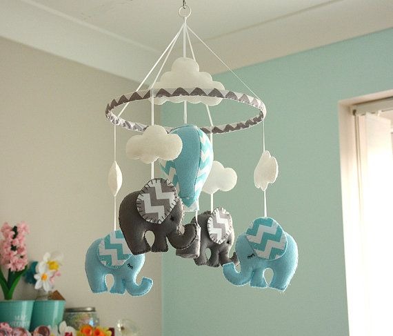 Blue Baby Boy Elephant Mobile Welcome to Flossytots This Elephant Mobile is MADE TO ORDER This mobile consists of 4 elephants, made using premium wool blend felt in ice blue/aqua chevron and grey /grey chevron. Above each elephant is a cloud. Hanging in the centre is a hot air balloon using the same colours used on the elephants. These mobiles are original Flossytots designs and are carefully cut and handstitched with lots of care and attention to detail. They make a beautiful ...