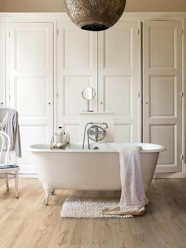 Los armarios blancos con cuarterones, la lámpara metálica árabe o la bañera exenta con patas son elementos simples que crean un ambiente de máxima calidez.