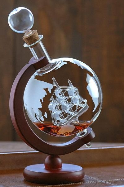 """Embrace your love of travel, adventure and whiskey with these stunning, mouth blown, lead-free glass decanters. Your guests will admire the artfully detailed antique ship encased in the etched globe decanter. Etched globe lead-free glass Detailed antique ship encased in the decanter Mahogany stained wood display Dimensions: 10"""" H X 4- 1/2"""" W X 6"""" D Capacity: 35 oz. #bourbonandboots"""
