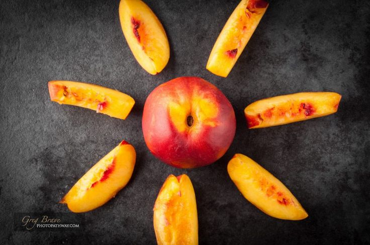 Yellow nectarine peach - whole and sliced on dark grunge background. Top view