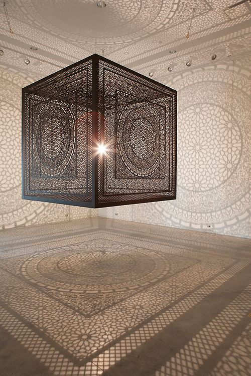 In this amazing light and shadow installation by Anila Quayyum Agha, we see a large-scale patterned wood cube with an interior light source that projects brilliant shadow patterns on the surrounding walls.