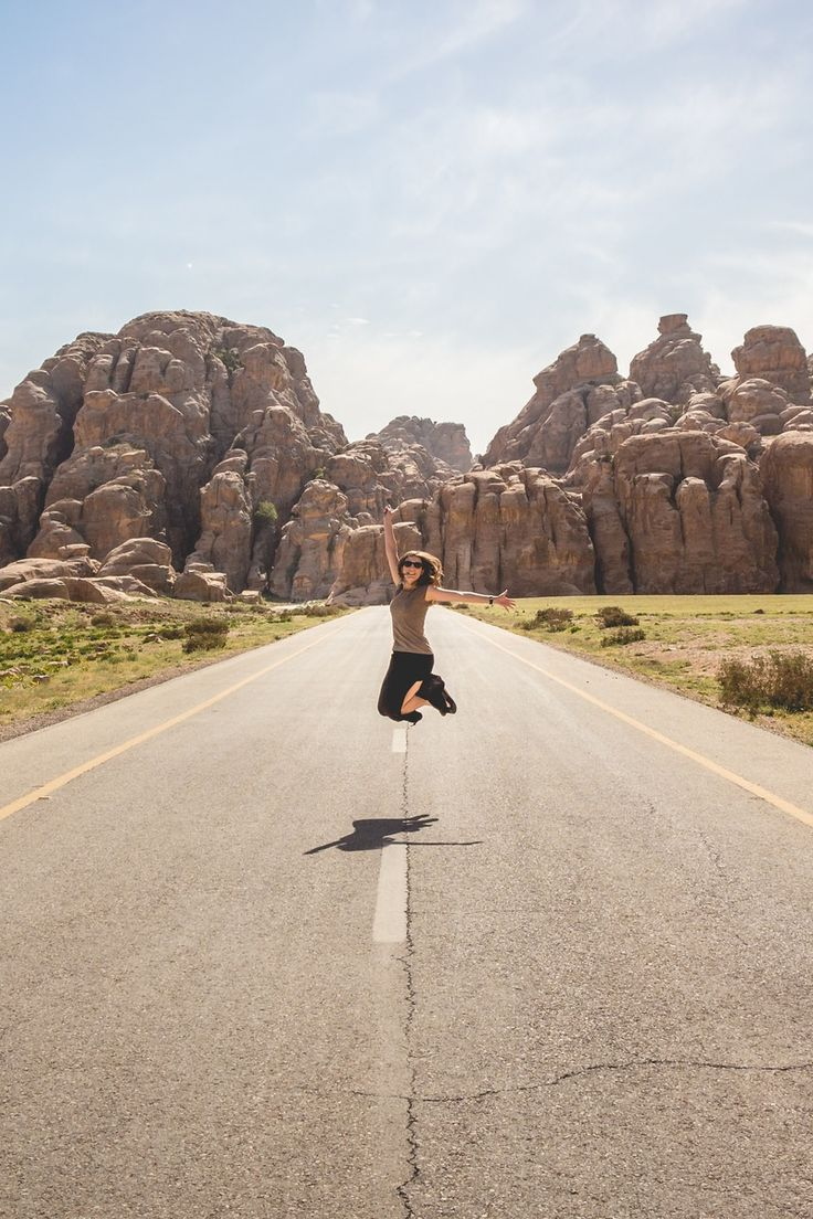 Woman in Brown Shirt Jumping Shot in Middle of Gray Asphalt Road Photography during Daytime