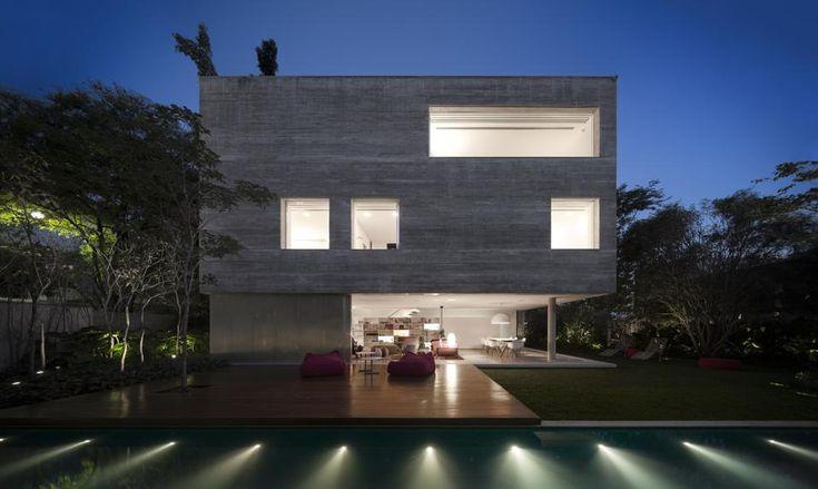 Villa in Brasile con giardino tropicale. Un cubo in calcestruzzo grigio, spezzato al pianterreno da un living che sconfina in un'ampio terrazzo con deck in legno, in piena relazione con il giardino.