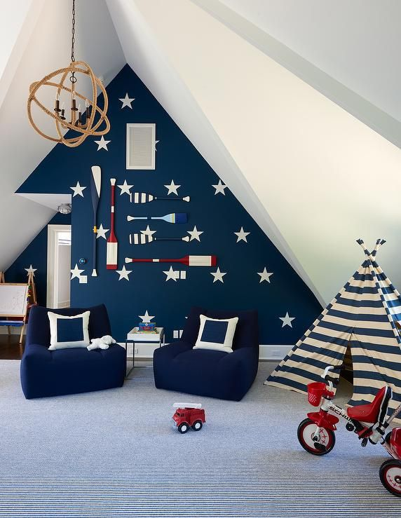 Under a vaulted ceiling, this gorgeous nautical kids playroom features a navy blue accent wall accented with white star stencils and mounted blue and white oars.