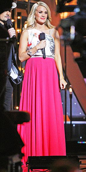 "Carrie Underwood's 11 Glam CMA Looks | PETALS AND PINK | The look that inspired a thousand ""Is that a crop top?!""s in the PEOPLE newsroom: Carrie's two-piece one-shoulder Theia look, consisting of a floral bodice and flowing magenta skirt. (And for the record, yes, it is a crop top!)"