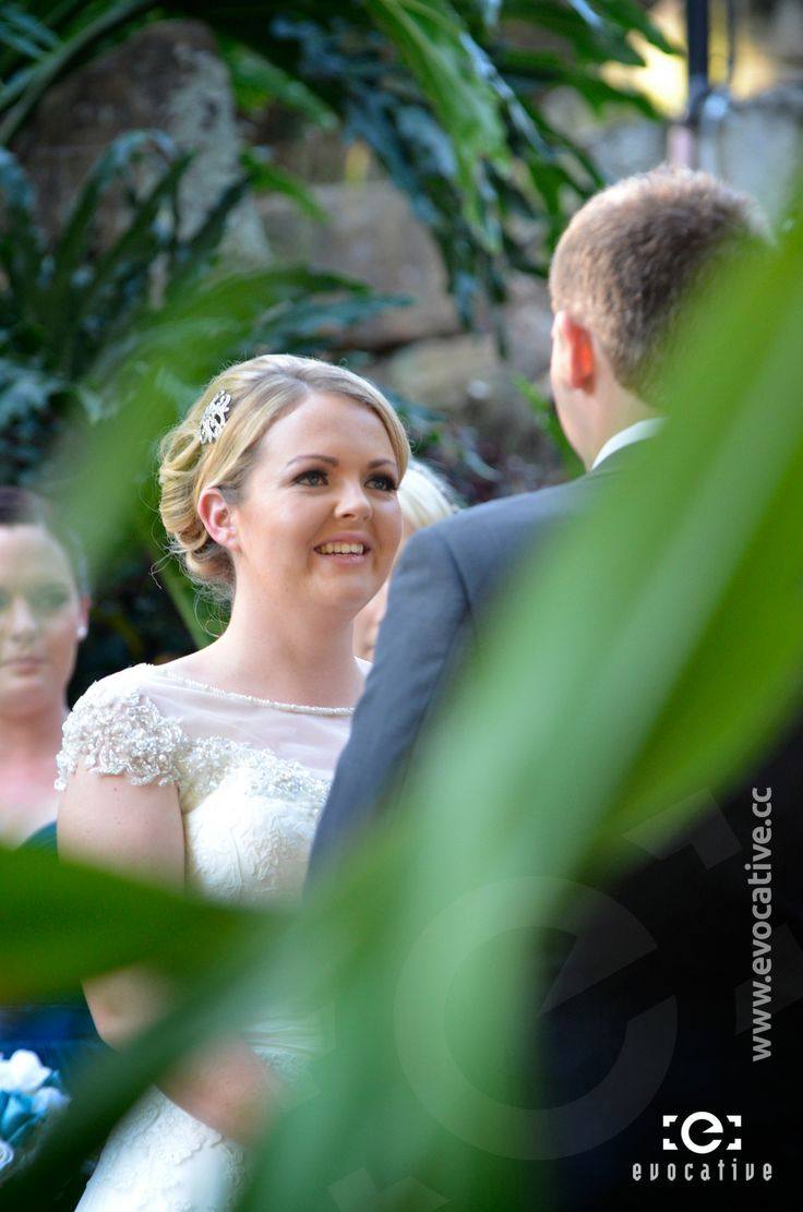 A smiling bride through the plants that surrounded the outdoor wedding ceremony, at Woodlands of Marburg. #WeddingPhotography