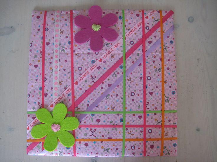 Een haarspeldjes bord, 45 x 45 cm, omtrokken met stof uit eigen atelier, bewerkt met linten in stof en satijn, twee grote bloemen van vilt met een applicatie als hartje, speciaal ontworpen voor een meisje dat heeeeel veel haarspeldjes heeft