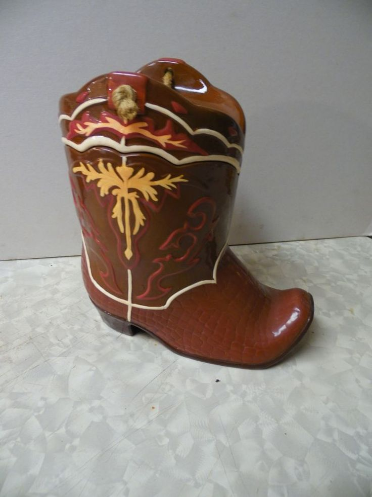 Ceramic Cookie Jar Western Cowboy Boot Texas, a beautiful ceramic cookie jar in the shape of a cowboy boot. Made by Roman, Inc. Classic southwestern colors - shades of red, brown,, and ivory. Made by Roman, Inc. Rope accent on lid.