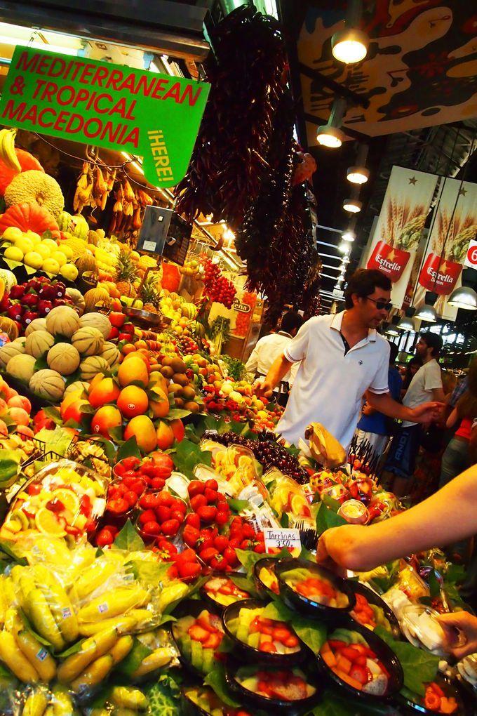 バルセロナのメインストリート、ランブラス通りにある『ボケリア市場(La Boqueria)』。鮮魚・肉・野菜・フルーツ・お菓子・調味料などなど、ありとあらゆる食材が彩も鮮やかに並び、買い物客でごった返している様子はまさに「バルセロナの台所」。バルセロナに行ったら絶対に外せないテッパンの観光スポットとしておすすめです。活気あふれるボケリア市場の雰囲気、ぜひあなたの目と舌で感じてください!