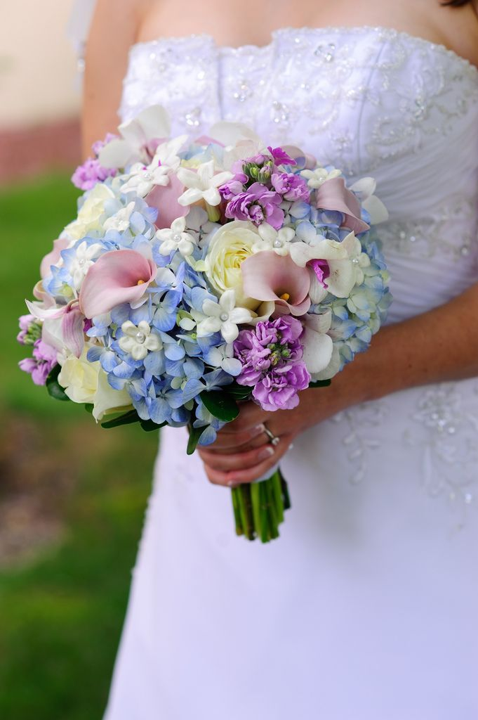 Soft and feminine bouquet in white, ivory, light blue, mauve pink, and lavender. Roses, calla lilies, hydrangea, stock, and stephanotis.