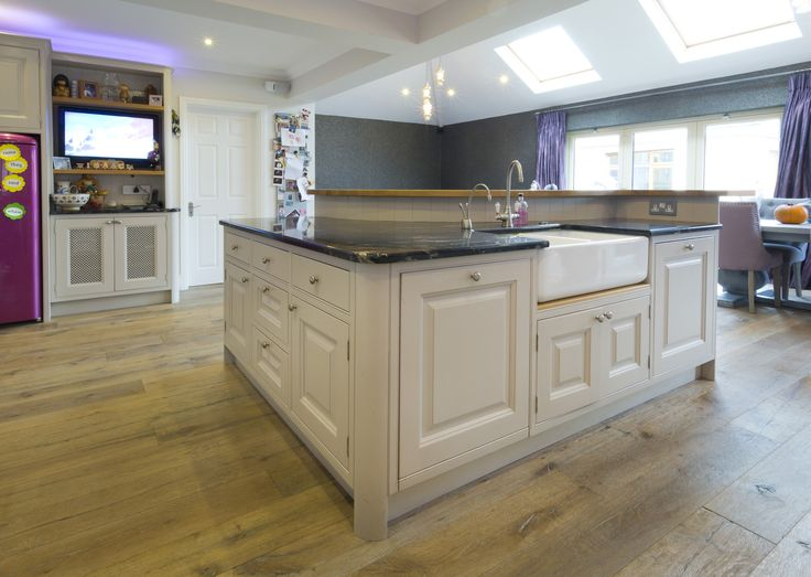 A raised panel door painted in Elephants Breath by Farrow & Ball completed with a Cosmic Black granite worktop, this in-frame kitchen fits seamlessly into place through its clever use of curved doors and posts. The solid oak breakfast bar mirrors this and provides the perfect place to entertain guests.
