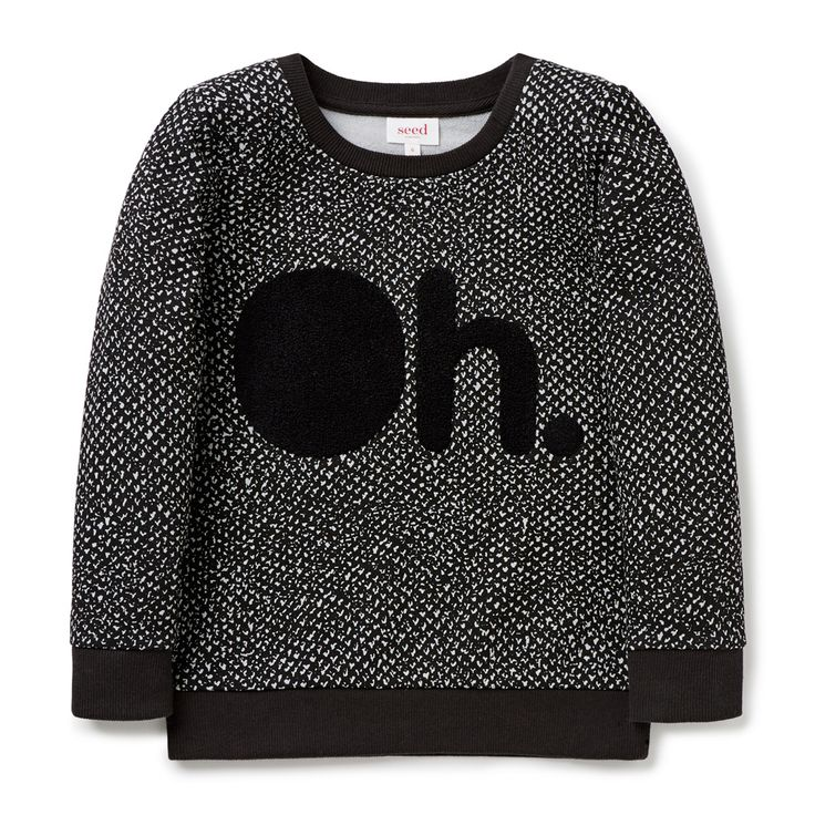 """100% Cotton French Terry Sweater. 2x2 rib trims. Features all over yardage print and chenille applique slogan """"Oh."""" on front panel. Regular fitting silhouette. Available in Vintage Black."""