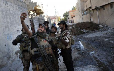 2016 in review: 50 powerful photos of war in Syria, Iraq, Libya and Yemen:      22 November 2016: A soldier from the Iraqi Special Forces takes a selfie on a street in the Aden district of Mosul after troops almost entirely retook the area from Islamic State.jihadists.  Thomas Coex/AFP