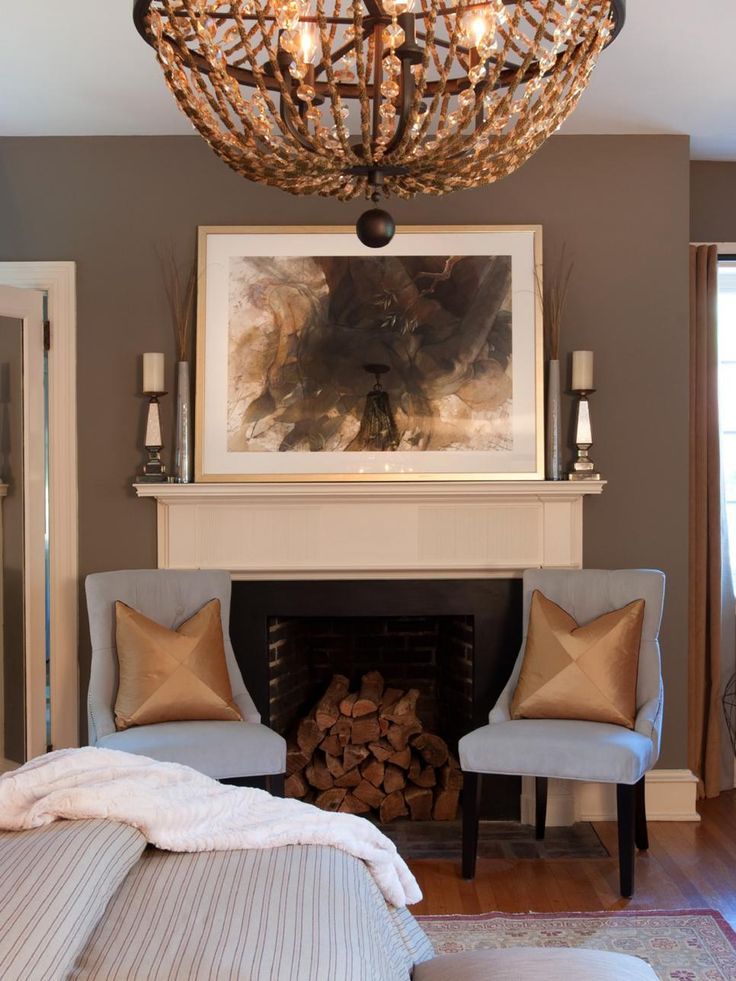 Gold is the predominant accent color in this lovely taupe brown bedroom. A chandelier holds court in the center of the room, while a fireplace flanked by two blue chairs with gold throw pillows serves as the room's focal point.