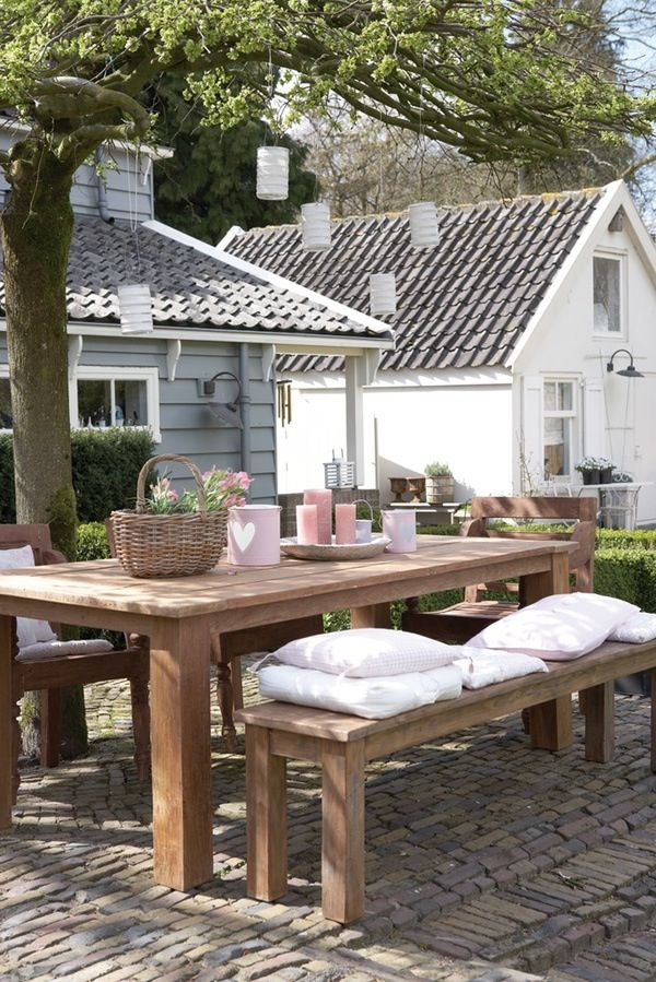 Simple outdoors table, bench, and chairs.