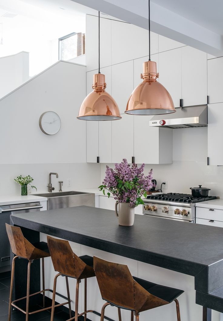 Modern kitchen with bronze bar chairs, and rose gold industrial pendant lights