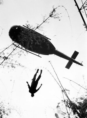 The body of a US paratrooper killed in action in the jungle near the Cambodian border is lifted up to an evacuation helicopter in War Zone C, May 14, 1966
