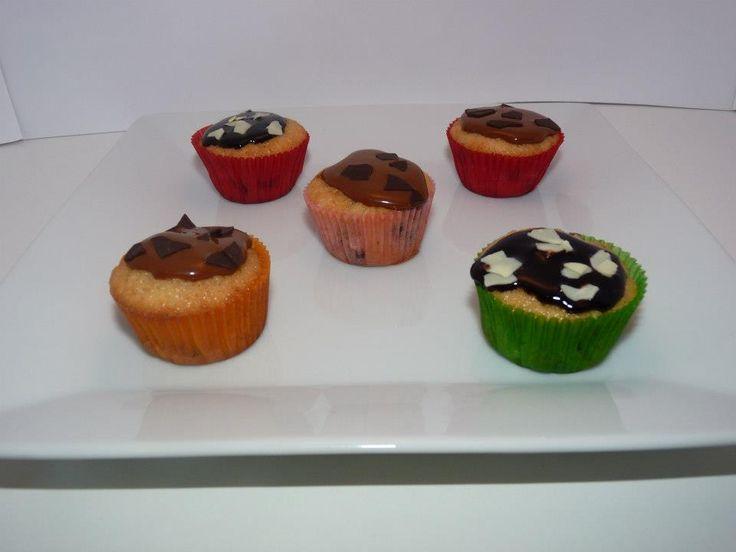 Minicupcakes con pepitas de chocolate y recubiertas de caramelo o chocolate con virutas de chocolate blanco o negro.