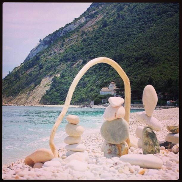 Composizioni artistiche di sassi di Portonovo in primo piano. Sullo sfondo, il profilo del Conero e l'acqua cristallina. #portonovo #conero #rivieradelconero #tourism #italy #vacanze #beaches