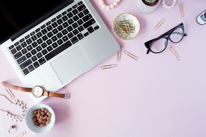 Top view home office desk frame. Feminine workspace with laptop, glasses, diary and golden clips, nuts on pink background. Flat lay composition for bloggers, designers, websites, magazines, social media, business owners and artists.