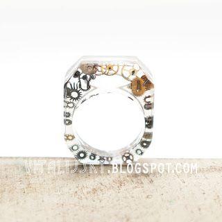Transparentny pierścień z trybikami w żywicy.