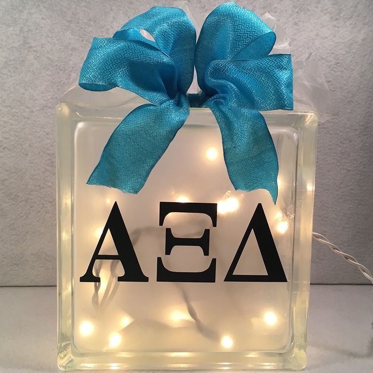 Share your sorority pride by lighting up your room with this hand crafted lighted 8x8 glass block. Frosted on the inside so the block won't scratch. Easily cleaned with a soft cloth. Images handcrafted in durable vinyl to last season after season. Electric light set evenly distributed throughout the inside of the block to display the image evenly. Each block beautifully decorated with French Ribbon. Ribbon may vary slightly depending upon availability. Custom designed with 3 sorority…