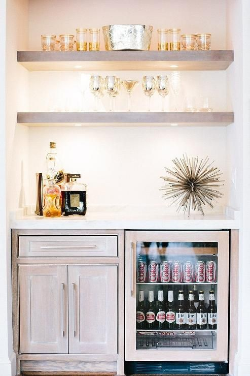 Fantastic bar nook is filled with gray wash floating shelves suspended over gray wash cabinets fitted with a glass front beverage fridge.