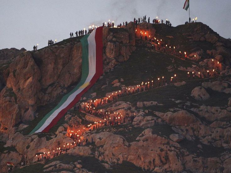 Iraqi Kurdish people carry fire torches up a mountain where a giant flag of Iraq's autonomous Kurdistan region is laid, as they celebrate Newroz Day, a festival marking their spring and new year, near Dahuk