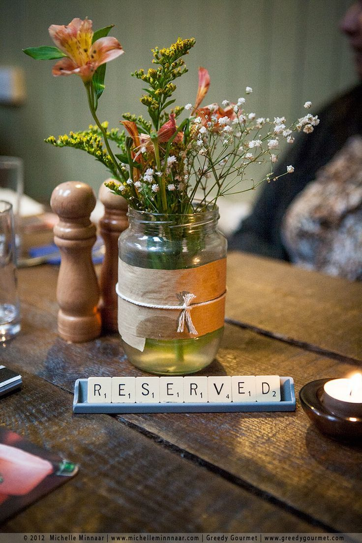 "Centerpieces can be simple and classy. The ""reserved"" sign made out of Scrabble letters is a nice touch."