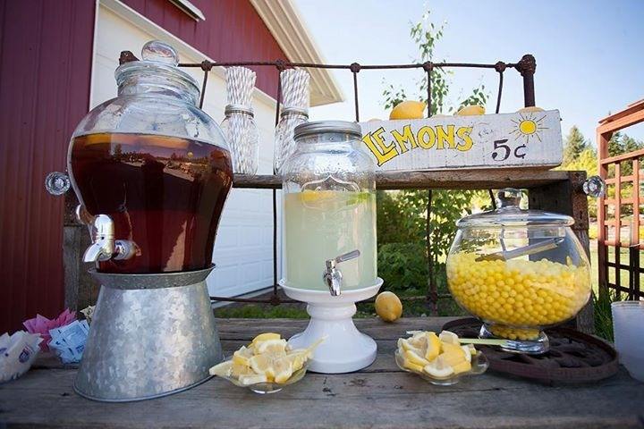The lemonade stand that I put together for a recent wedding... This greeted guests when they walked in before the ceremony. I think it turned out perfectly! The bench is a potting bench that belongs to my mom (designed by her and built by my uncle). It's complete with a partial bed frame at the back and it was the perfect table for this laid-back lemonade stand. I love looking at photos for ideas and I hope this helps someone!