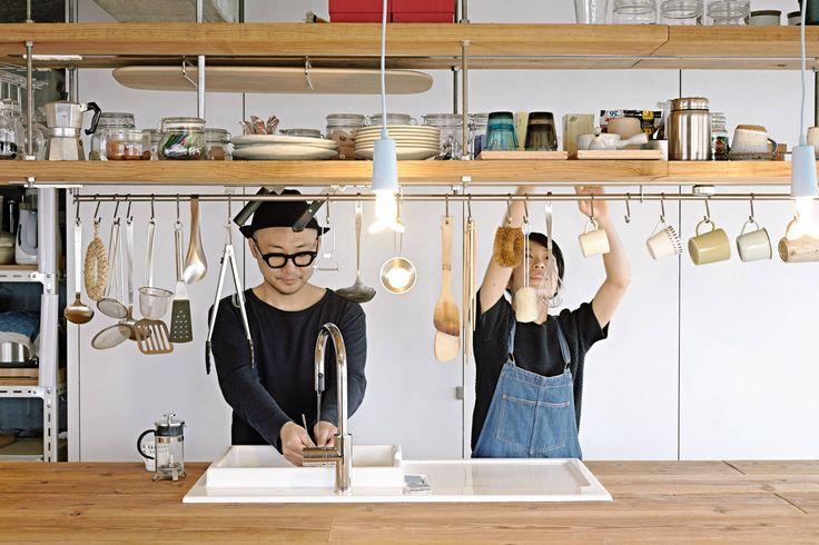 日常的に使う頻度の高い食器や調味料・お茶などの食料品、キッチン小物は、棚の中に仕舞いこむほどではないこともあります。ならば、うまくディスプレイして見せる収納にしてしまうのが使いやすいキッチンになること間違いなしです。こちらのお宅では、キッチンの作業台の頭上に長く二重に棚を設置して、食器や調味料などをうまく収め、キッチン小物やマグカップは棚下に渡してあるスチールレールに吊るす形で収納しています。木べらや杓子、菜箸などは箸立てのような器にさしていると、種類が多くなるほどに取り出すのが億劫になることも。吊るす収納ならば、洗ってすぐひっかけておくことができて衛生的にもよさそうです。