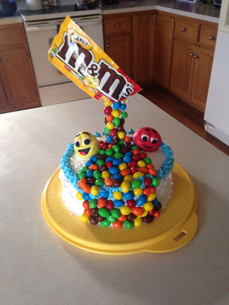 Anti gravity cake made by me, a 11! Year old it is so easy to do! Just frost a cake is straws or skewers in a bind and frost them them cover with whatever and put the wrapper on top and for the water fall effect just add your candy and press them in to the cake and go down. For the m&m characters just use fondant